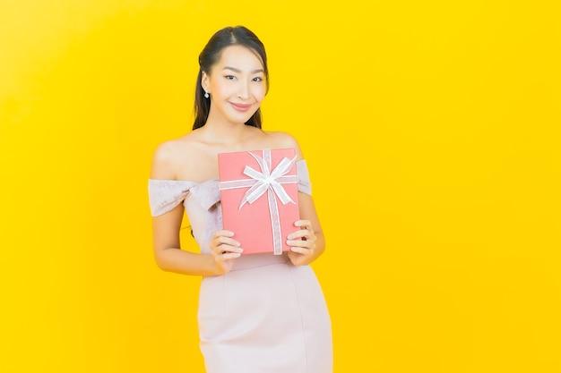 Schöne junge asiatische frau des porträts, die mit roter geschenkbox auf farbwand lächelt