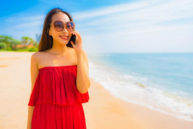 Schöne junge asiatische frau des porträts, die mobiltelefon oder handy auf dem strand und dem meer verwendet