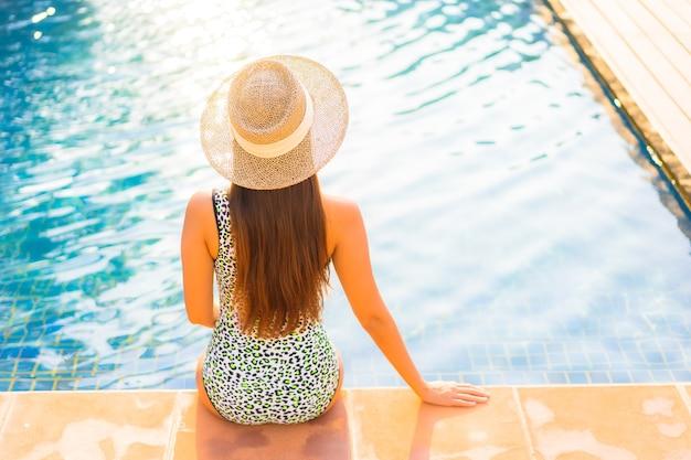 Schöne junge asiatische frau des porträts, die sich im urlaub am pool im resorthotel entspannt?