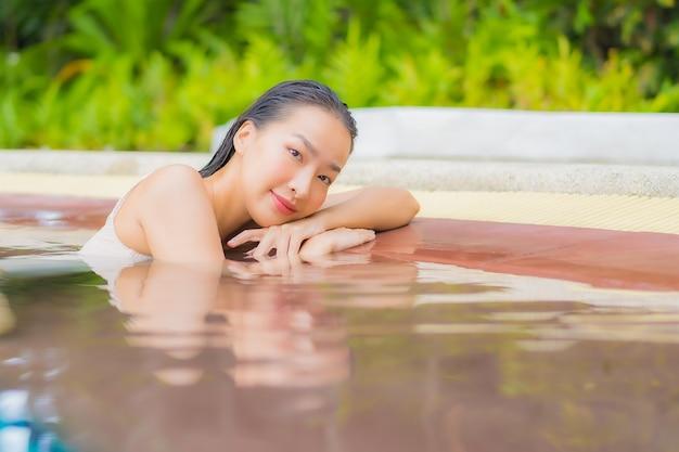 Schöne junge asiatische frau des porträts entspannen sich am außenpool im resort