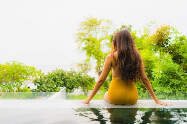 Schöne junge asiatische frau des porträts entspannen sich freizeit im swimmingpool am hotel und am erholungsort