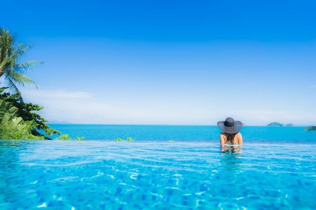 Schöne junge asiatische frau des porträts entspannen sich im luxusaußenpool im strandurlaubsort fast seeozean