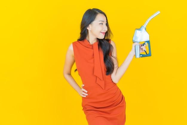 Schöne junge asiatische frau des porträts feul zapfsäule auf gelb