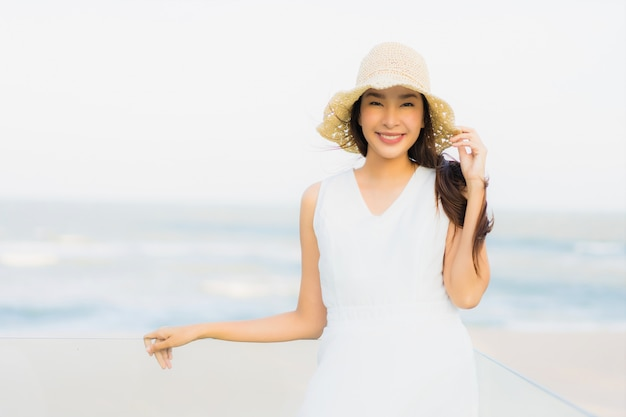 Schöne junge asiatische frau des porträts glücklich und lächeln auf dem strandmeer und -ozean