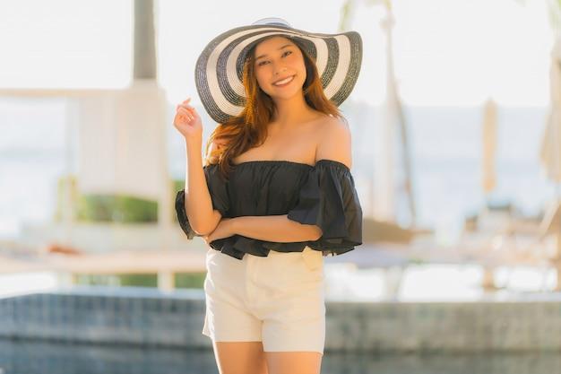 Schöne junge asiatische frau des porträts glücklich und lächeln mit reise in neary meer des hotels und strand