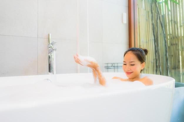 Schöne junge asiatische frau des porträts in der badewanne für nehmen ein bad