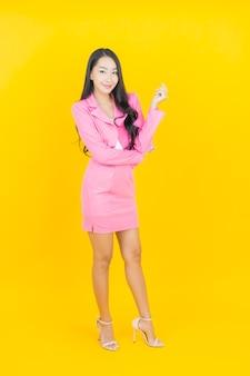 Schöne junge asiatische frau des porträts lächeln mit aktion auf gelber farbwand Kostenlose Fotos
