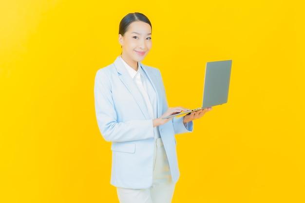 Schöne junge asiatische frau des porträts lächeln mit computerlaptop auf lokalisiertem hintergrund