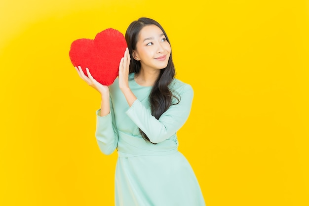 Schöne junge asiatische frau des porträts lächeln mit herzkissenform auf gelb