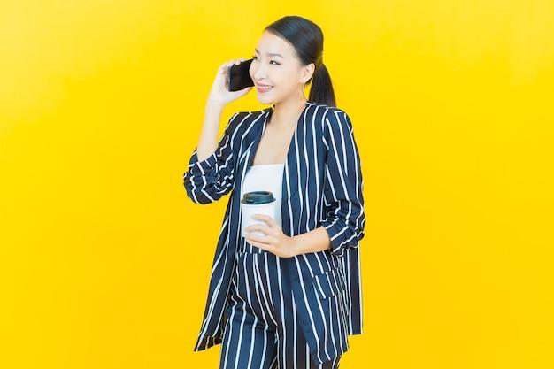 Schöne junge asiatische frau des porträts lächeln mit intelligentem handy auf farbhintergrund