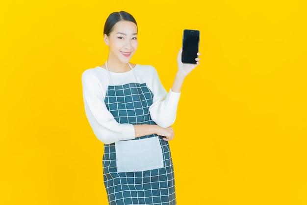Schöne junge asiatische frau des porträts lächeln mit intelligentem handy auf gelb