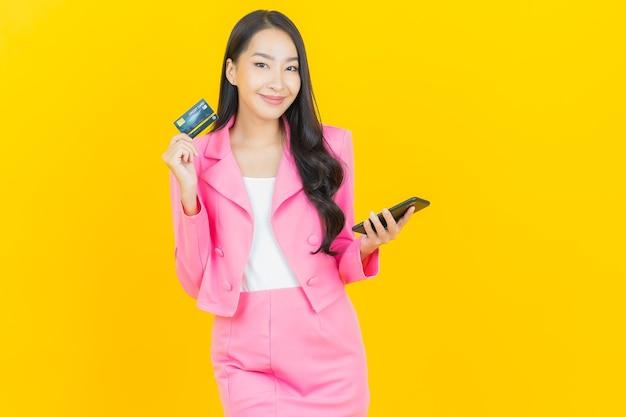 Schöne junge asiatische frau des porträts lächeln mit intelligentem handy auf gelber farbwand
