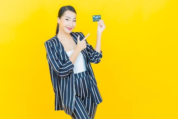 Schöne junge asiatische frau des porträts lächeln mit kreditkarte auf farbhintergrund