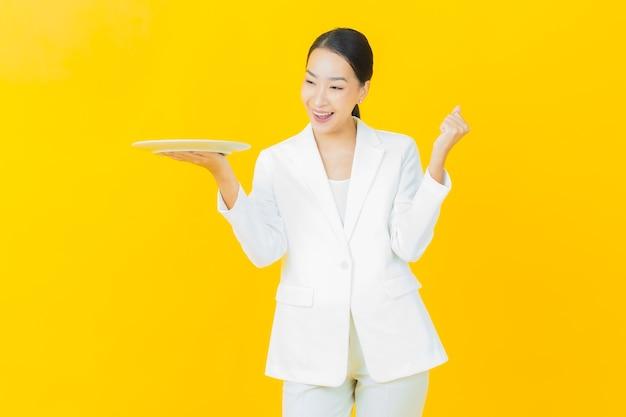 Schöne junge asiatische frau des porträts lächeln mit leerem tellerteller auf farbwand