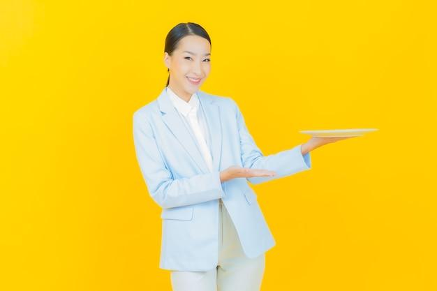 Schöne junge asiatische frau des porträts lächeln mit leerem tellerteller auf gelb
