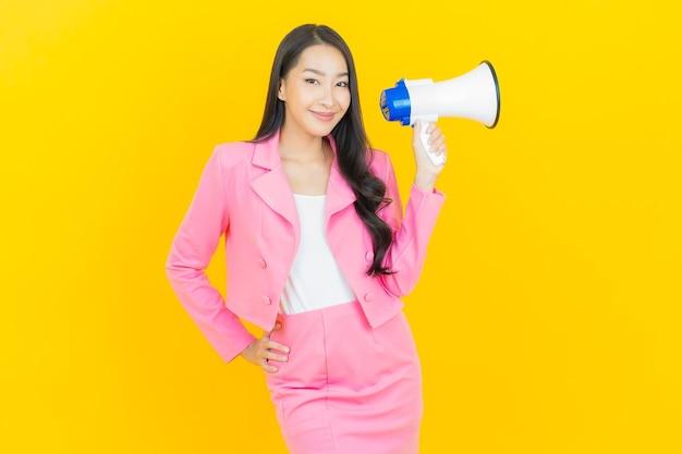 Schöne junge asiatische frau des porträts lächeln mit megaphon auf gelber farbwand
