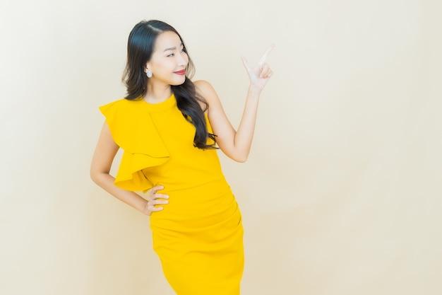 Schöne junge asiatische frau des porträts lächelt auf beige wand