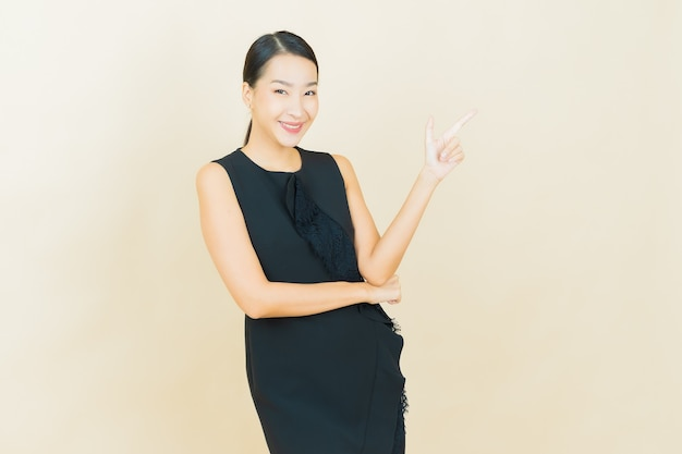 Schöne junge asiatische frau des porträts lächelt auf farbwand