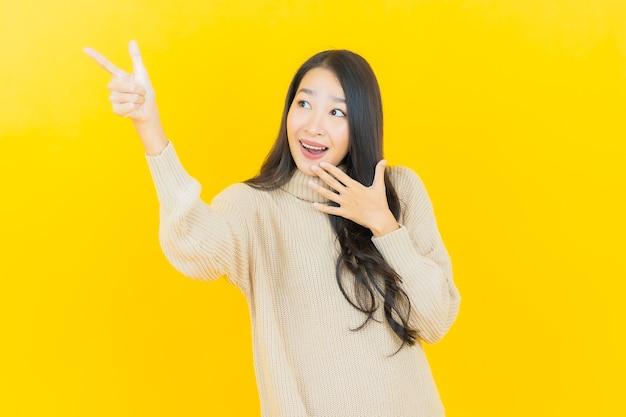 Schöne junge asiatische frau des porträts lächelt mit aktion auf gelber wand