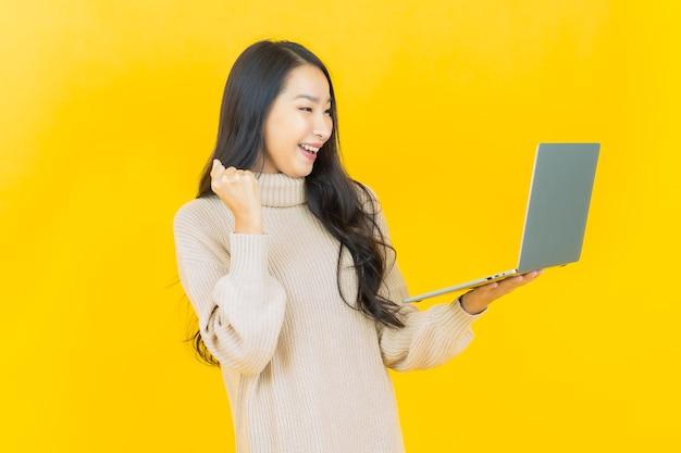 Schöne junge asiatische frau des porträts lächelt mit computerlaptop auf lokalisiertem hintergrund