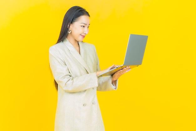 Schöne junge asiatische frau des porträts lächelt mit computerlaptop auf lokalisierter wand