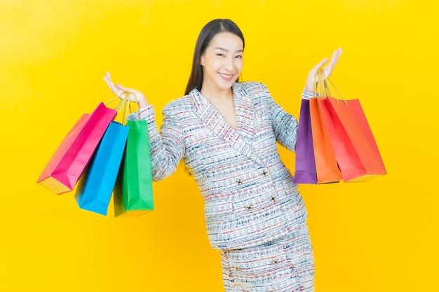 Schöne junge asiatische frau des porträts lächelt mit einkaufstasche auf farbwand