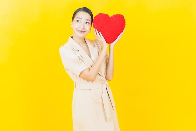 Schöne junge asiatische frau des porträts lächelt mit herzkissenform auf farbwand