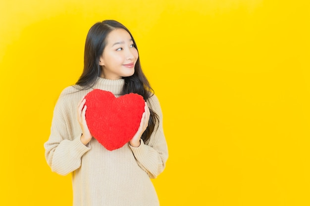 Schöne junge asiatische frau des porträts lächelt mit herzkissenform auf gelber wand