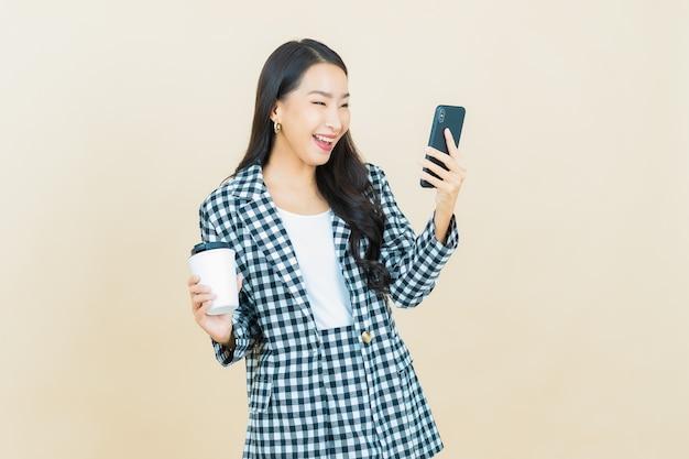Schöne junge asiatische frau des porträts lächelt mit intelligentem handy auf beige