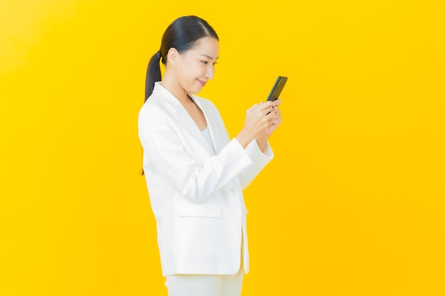 Schöne junge asiatische frau des porträts lächelt mit intelligentem handy auf farbwand