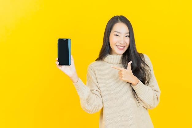 Schöne junge asiatische frau des porträts lächelt mit intelligentem handy auf gelber wand