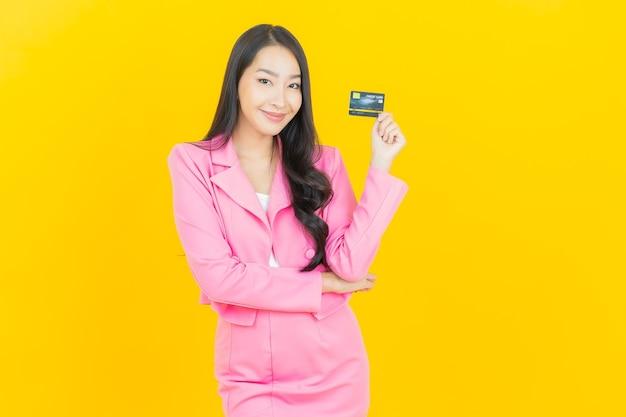 Schöne junge asiatische frau des porträts lächelt mit kreditkarte auf gelber farbwand