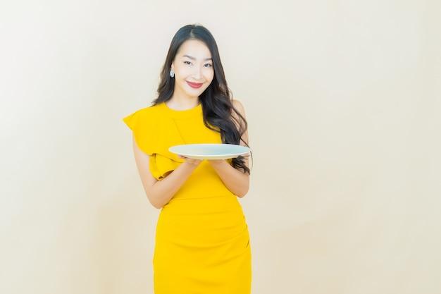 Schöne junge asiatische frau des porträts lächelt mit leerem tellerteller auf beige wand