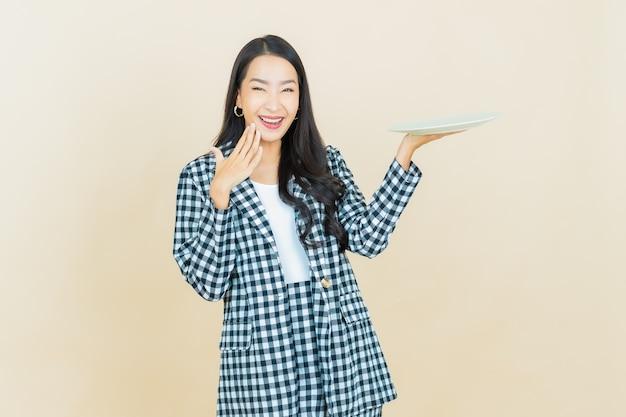 Schöne junge asiatische frau des porträts lächelt mit leerem tellerteller auf beige