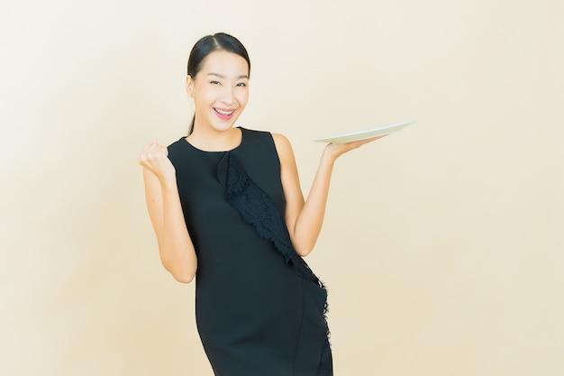 Schöne junge asiatische frau des porträts lächelt mit leerem tellerteller auf farbwand