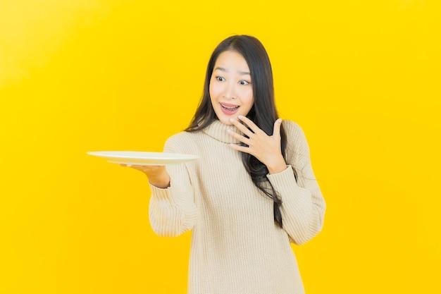 Schöne junge asiatische frau des porträts lächelt mit leerem tellerteller auf gelber wand