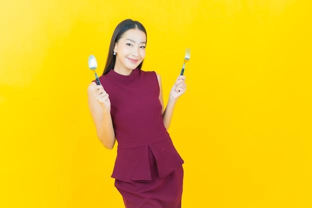 Schöne junge asiatische frau des porträts lächelt mit löffel und gabel auf gelber wand