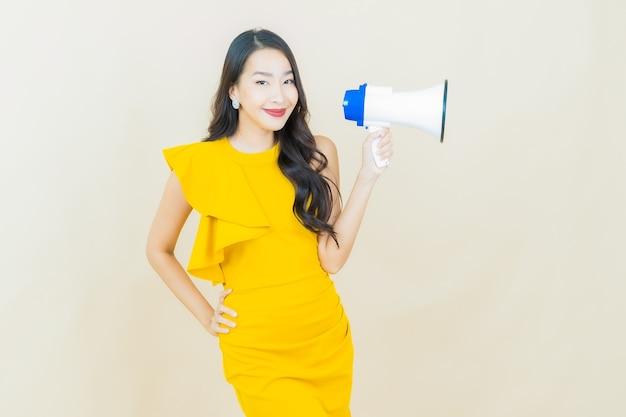 Schöne junge asiatische frau des porträts lächelt mit megaphon auf beige wand