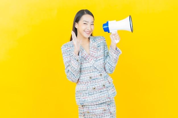 Schöne junge asiatische frau des porträts lächelt mit megaphon auf farbwand