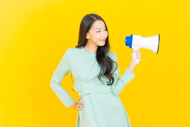 Schöne junge asiatische frau des porträts lächelt mit megaphon auf gelb