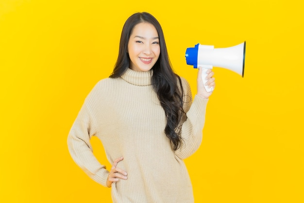 Schöne junge asiatische frau des porträts lächelt mit megaphon auf gelber wand