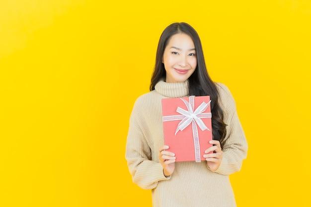 Schöne junge asiatische frau des porträts lächelt mit roter geschenkbox auf gelber wand