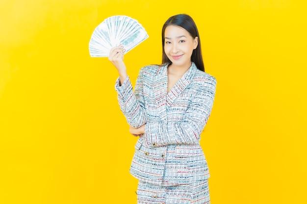 Schöne junge asiatische frau des porträts lächelt mit viel bargeld und geld auf farbwand