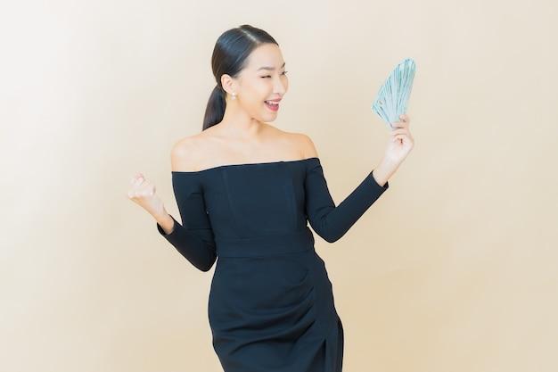 Schöne junge asiatische frau des porträts lächelt mit viel bargeld und geld auf gelb