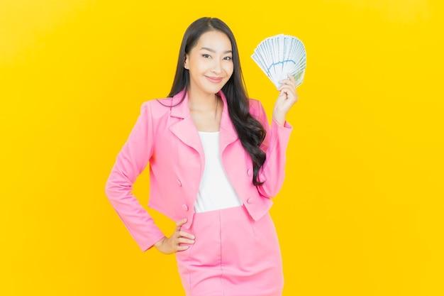 Schöne junge asiatische frau des porträts lächelt mit viel bargeld und geld auf gelber farbwand
