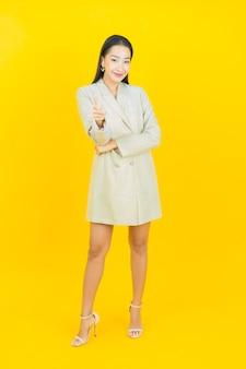 Schöne junge asiatische frau des porträts lächelt und zeigt nach vorne auf der farbwand