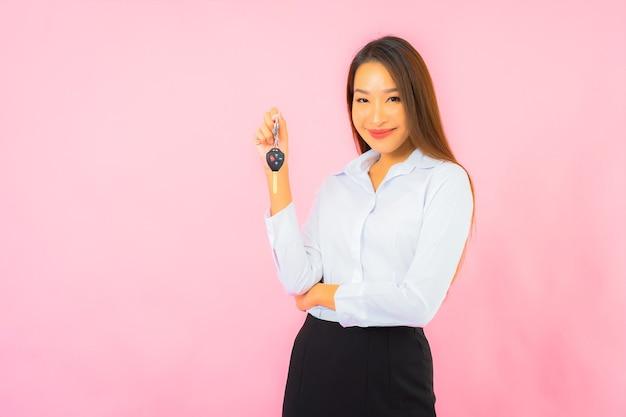 Schöne junge asiatische frau des porträts mit autoschlüssel auf rosa isolierter wand