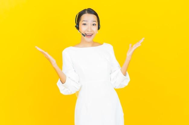 Schöne junge asiatische frau des porträts mit callcenter-kundenbetreuungszentrum auf gelb on
