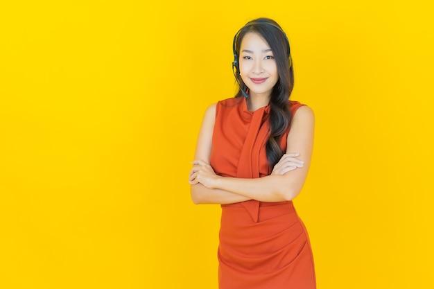 Schöne junge asiatische frau des porträts mit callcenter-kundenbetreuungszentrum auf gelb