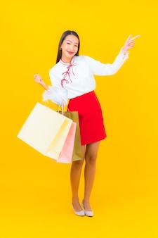 Schöne junge asiatische frau des porträts mit einkaufstasche und kreditkarte auf gelb